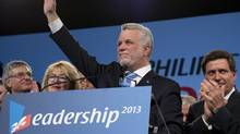 The new Quebec Liberal Party Leader Philippe Couillard waves to delegates as interim leader Jean-Marc Fournier, left, Couillard's wife Suzanne Pilote and runner up Pierre Moreau right, look on Sunday, March 17, 2013 at the leadership convention in Montreal. (Jacques Boissinot/THE CANADIAN PRESS)
