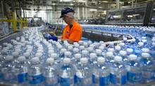 A worker inspects bottles of water at the Nestlé Waters Canada plant near Guelph, Ont., on Jan. 16, 2015. (Kevin Van Paassen/Bloomberg)