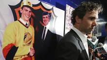 Vancouver Canucks' Trevor Linden is interviewed after announcing his retirement as a photograph of himself with Pat Quinn at the NHL entry draft in 1988 hangs on the wall behind him, in Vancouver, B.C., on Wednesday June 11, 2008. (DARRYL DYCK/The Canadian Press)