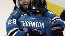 San Jose Sharks' Brent Burns (88) celebrates with teammate Joe Thornton after scoring the go-ahead goal during the third period of an NHL game against the Ottawa Senators on Saturday, Oct. 12, 2013, in San Jose, Calif. (Marcio Jose Sanchez/AP)