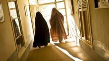 Women don burkas on their way out the door. Although many women in Kandahar do not often venture outside their home compound walls, on the rare occasion when they do they cover from head to toe. (Paula Lerner/Paula Lerner/Aurora Photos)