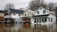 Men stand on the front porch of a home in a flooded residential area in Gatineau, Quebec, Canada, May 7, 2017. (CHRIS WATTIE/REUTERS)