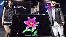 "Masaaki Osumi, an executive for Japanese electronics company Toshiba, poses with models next to the company's 55-inch sized glasses-free 3D television called the ""Regza 55X3', which has ""Quad Full High Definition"" (QFHD) with a 3,840 x 2,160-pixel LCD display and which shows 2D and 3D high definition images, during a preview at Asia's largest electronics trade show CEATEC in Chiba City, suburban Tokyo, on October 3, 2011. (YOSHIKAZU TSUNO/YOSHIKAZU TSUNO/AFP/Getty Images)"