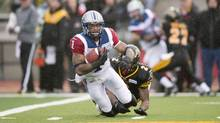 Montreal Alouettes' Arland Bruce is brought down by Hamilton Tiger-Cats defensive back Evan McCollough during first half East Division semifinal CFL action in Guelph, Ont., on Sunday, Nov. 10, 2013. (Frank Gunn/THE CANADIAN PRESS)