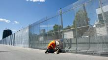 A construction worker puts up a three metre high steel security fence outside the Toronto Metro Convention Centre for the upcoming Toronto G20 summit in Toronto on Tuesday, June 8, 2010. (Nathan Denette / The Canadian Press/Nathan Denette/The Canadian Press)