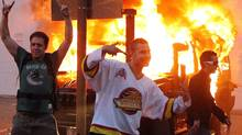 People pose in front of a burning vehicle on June 15, 2011 in Vancouver, Canada. Vancouver broke out in riots after their hockey team the Vancouver Canucks lost in Game Seven of the Stanley Cup Finals. (Bruce Bennett/Getty Images)