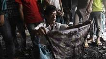 A man shows a piece of cloth which he says belong to his sister-in-law, a missing worker after a devastating fire in a garment factory which killed more than 100 people, in Savar Nov. 26, 2012. (ANDREW BIRAJ/REUTERS)