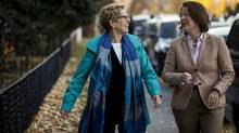 Ontario Premier Kathleen Wynne, left, walks with Alberta Premier Alison Redford to a popular coffee shop in Calgary, Alta., Friday, Oct. 25, 2013. (Jeff McIntosh/THE CANADIAN PRESS)