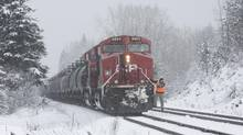 A worker steps off of a CP Rail train onto snow covered tracks near Malakwa, B.C., Dec. 22, 2015. (JASON FRANSON For The Globe and Mail)