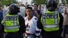 A Vancouver Canucks fan confronts the police during riots after the Canucks lost Game 7 of the NHL Stanley Cup final hockey game in Vancouver, British Columbia June 15, 2011. (Mike Carlson/ The Globe and Mail/Mike Carlson/ The Globe and Mail)