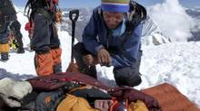 A rescuer speaks to a survivor in the wake of a deadly avalanche in Nepal. (Garrett Madison/Associated press)