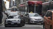 Streetcars and cars compete for space on a crowded Toronto street this month. (Fred Lum/The Globe and Mail)