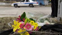 Makeshift memorial at police tape line near the scene of a multiple fatal stabbing in northwest Calgary, Alberta on Tuesday, April 15, 2014. (Larry MacDougal/The Canadian Press)