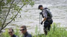 A Police search dog unit searches the banks of the Credit River in Hewick Meadows Park in Mississauga, Ont., after police discovered a female severed head on Thursday August 16, 2012. Investigators said they found a severed human foot the in the area the previous day. (Aaron Vincent Elkaim/THE CANADIAN PRESS)