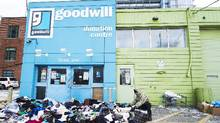 A man cleans up a pile of clothes and items left outside a closed Goodwill donation centre in Toronto on Jan. 19. (Nathan Denette/THE CANADIAN PRESS)