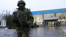 An armed man patrols at the airport in Simferopol, Crimea February 28, 2014. A group of armed men in military uniforms have seized the main regional airport in Simferopol, Crimea, Interfax news agency said early on Friday. (David Mdzinarishvili/Reuters)