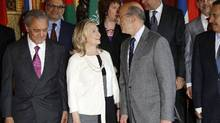 "French Foreign Minister Alain Juppe, right, turns to speak to U.S. Secretary of State Hillary Clinton as Saudi Arabia's Foreign Minister Saud Al-Faysal Bin Abdelaziz, left, stands nearby during the family photo at the ""Friends of Syria"" meeting in Paris on Thursday. (Benoit Tessier/Reuters/Benoit Tessier/Reuters)"