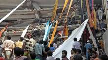 Rescue workers use clothes to bring down survivors and bodies after an eight-story building housing several garment factories collapsed in Savar, near Dhaka, Bangladesh, Wednesday, April 24, 2013. Better Work Bangladesh follows a Cambodian model to improve safety at factories. (A.M. Ahad/AP)