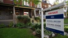 A for-sale sign is seen in front of a home in Toronto. (Galit Rodan/The Globe and Mail)