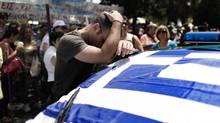 A striking municipal police officer reacts as he leans on a car with a Greek flag during a protest Friday in Athens against new austerity cuts that will affect thousands of public sector workers, in Athens, Friday, July 12, 2013. The hope that spring's dearth of bad news from Greece could spill into summer, spurring growth in the local economy, shattered last week amid fresh fears of added austerity. (Petros Giannakouris/AP)