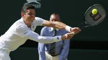 Milos Raonic plays a return to Roger Federer (Ben Curtis/AP Photo)