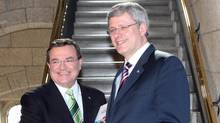 Finance Minister Jim Flaherty and Prime Minister Stephen Harper shake hands as they make their way to the House of Commons to deliver the federal budget on Parliament Hill in Ottawa on Tuesday March 22, 2011. (Fred Chartrand/The Canadian Press/Fred Chartrand/The Canadian Press)