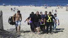 Christopher Myers is carried off Ballston Beach in Truro, Mass., after sustaining bite wounds to his legs while swimming on Monday. (Eric williams/The Associated Press)