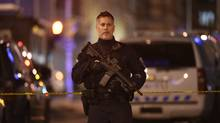 A member of the Emergency Services Unit of the Ottawa police force has a machine gun slung over his shoulder while manning a road block at Albert and Metcalfe Sts, in Ottawa on Oct 22 2014. Much of downtown Ottawa was shutdown after a gunmen shot and skilled a member of the Canadian Forces who was staring guard at the War Memorial near Parliament Hill. The gunman then made his way to Parliament Hill where he gained entry and began shooting. The shooter was taken down by Hill security forces on Oct 22 2014. (HANDOUT/THE CANADIAN PRESS)