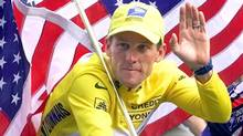 This July 23, 2000 file photo shows Tour de France winner Lance Armstrong riding down the Champs Elysees with an American flag after the 21st and final stage of the cycling race in Paris. (Associated Press)