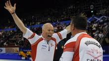 Canadian skip Glenn Howard, left, celebrates with third Wayne Middaugh after his rink beat Scotland 8-7 to win the gold medal at the world men's curling championship in Basel, Switzerland, Sunday. (Michael Burns)