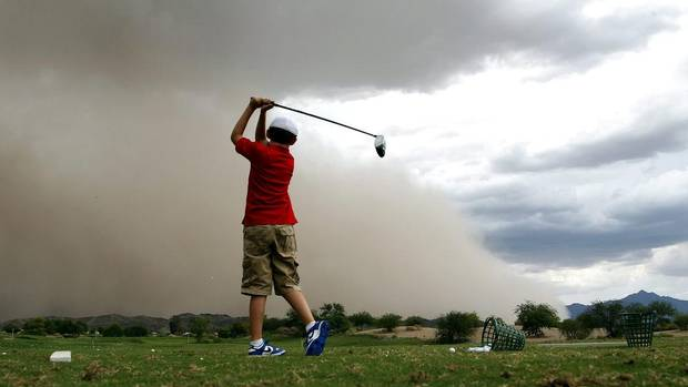 A lone golfer tries to get in a few more swings on the practice range as a sand storm hits the Phoenix metro area Sunday, July 29, 2012, in Laveen, Ariz. (Ross Franklin/AP)