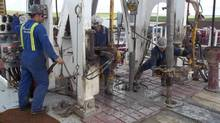 Craig Paradis (L) of Advance Drilling, operates the brake handle on a drilling rig for Crescent Point Energy as two roughnecks add a pipe extension to drill deeper into the Bakken formation near Oungre, Saskatchewan in this June 20, 2012 file photo. (Reuters)