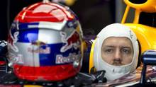 Red Bull driver Sebastian Vettel of Germany sits in his car during a delay for the start of the morning practice session at the Canadian Grand Prix, Saturday, June 8, 2013 in Montreal. (Paul Chiasson/THE CANADIAN PRESS)