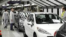 An employee works in the assembly line of the Peugeot 207 at the PSA Peugeot Citroen plant in Poissy, near Paris, in this January 27, 2012 file photo. (BENOIT TESSIER/REUTERS)