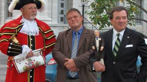 With Kingston's town crier and historian Arthur Milnes by his side, Finance Minister Jim Flaherty conducts a walking tour of Sir John A. Macdonald's old haunts on Sept. 29, 2011.