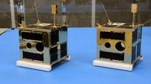 Two nano-satellites dubbed Montreal and Toronto as they appeared in the University of Toronto Space Flight Laboratory before heading to a launch in Russia. Engineers suspect that Montreal is still stuck inside the rocket that lofted both of the toaster-sized spacecraft into orbit.
