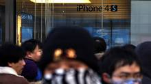The remains of eggs can be seen on the window of an Apple store as a crowd waits outside in the Beijing district of Sanlitun on Jan. 13, 2012. (David Gray/Reuters/David Gray/Reuters)