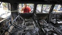 A Buddhist monk looks through the window of a burnt car after Muslims attacked and set fire to a temple in Cox's Bazar October 1, 2012. Bangladesh accused Muslim Rohingya refugees from Myanmar on Monday of involvement in attacks on Buddhist temples and homes in the southeast and said the violence was triggered by a photo posted on Facebook that insulted Islam. (ANDREW BIRAJ/REUTERS)