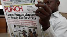 A man reads a local newspaper with headline news about Ebola in Lagos, Nigeria, on Aug. 5, 2014. (Sunday Alamba/AP)