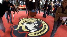 Journalists and cameramen avoid stepping on the Ottawa Senators logo on the floor of their dressing room following team practice in Ottawa Wednesday, April 18, 2007. (The Canadian Press)