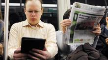 A commuter reads on an e-reader next to a newspaper reader while riding the subway in Cambridge, Massachusetts, March 18, 2011. (BRIAN SNYDER)