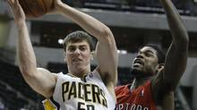 In this file photo, Indiana Pacers forward Tyler Hansbrough, left, grabs a rebound from Toronto Raptors forward Amir Johnson during the second quarter of an NBA basketball game in Indianapolis, Monday, Jan. 11, 2010. The Raptors have signed the former Indiana Pacers free agent to a multi-year contract according to multiple reports. (Darron Cummings/AP)