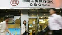 Pedestrians pass an Industrial & Commercial Bank of China branch in Hong Kong in a file photo. ICBC, the world's biggest bank by market value, bought a 20-per-cent stake in South Africa's Standard Bank in 2007. Since then, other Chinese banks have invested in Africa. (Kin Cheung/AP)