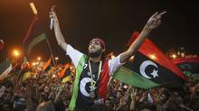 People celebrate the capture in Tripoli of Moammar Gadhafi's son and one-time heir apparent, Seif al-Islam, at the rebel-held town of Benghazi, Libya, early Monday. (Alexandre Meneghini/Alexandre Meneghini/AP)