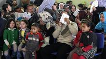 Syrian families wait their turn to register at the UNHCR centre in the northern city of Tripoli, Lebanon, March 6, 2013. (Bilal Hussein/AP)