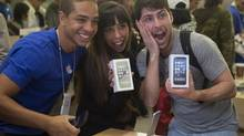 Alejandro de Rosa and Melisa Racineti of Buenos Aires, Argentina pose with their new Apple iPhone 5s phones with Apple employee Jay at the Apple Retail Store on Fifth Avenue in Manhattan, New York September 20, 2013. (ADREES LATIF/REUTERS)