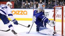 Leafs goalie Frederik Andersen (31) stretches for a tipped shot that goes wide of the net off the stick of Tampa Bay Lightning defenceman Andrej Sustr (62). (Tom Szczerbowski/USA Today Sports)