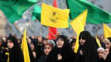 Iranian women wave Islamic flags Iranians wave Islamic flags while chanting against the al-Qaida inspired Islamic State in Iraq and the Levant, ISIL, during a rally in central Tehran, Iran, Tuesday, June 24, 2014. (Ebrahim Noroozi/AP)