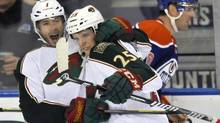 Minnesota Wild's Matt Cullen (L) celebrates his goal with Jonas Brodin as Edmonton Oilers' Eric Belanger (R) skates by during the second period of their NHL game in Edmonton February 21, 2013. (DAN RIEDLHUBER/REUTERS)
