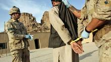 A suspected Taliban prisoner is searched, handcuffed, and processed by Canadian soldiers in northern Kandahar province, Afghanistan, on May 10, 2006. (JOHN D MCHUGH/AFP/Getty Images)